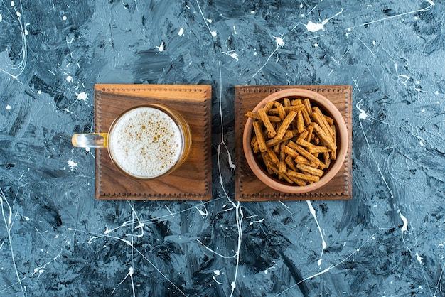 Breadcrumbs and beer on a board, on the marble background.
