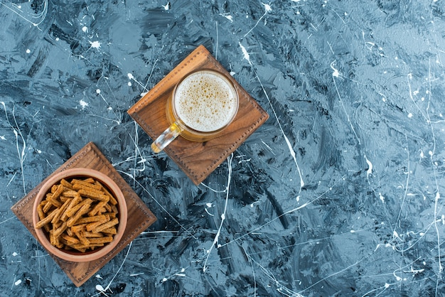 Breadcrumbs and beer on a board, on the marble table.