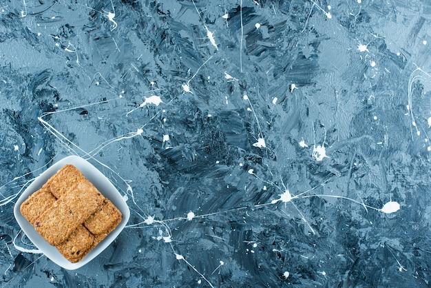 大理石の背景に、プレート上のパンくずリスト。