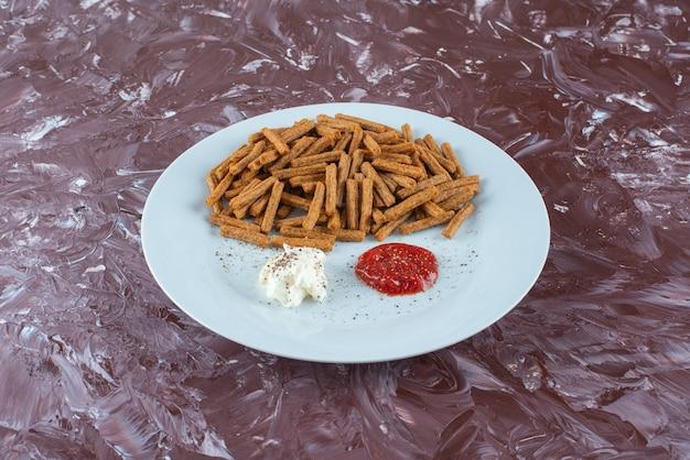 대리석 테이블에 접시에 소스와 빵 부스러기.