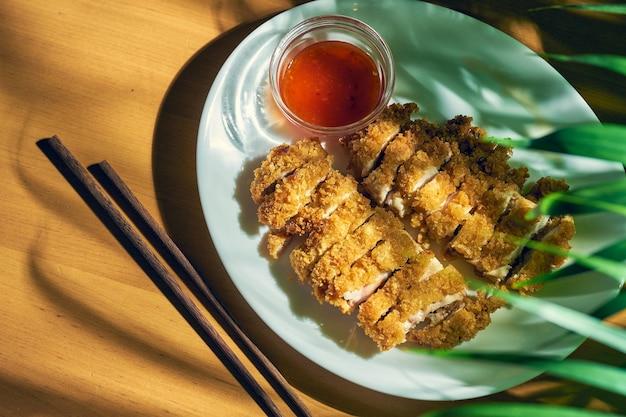 Куриный стейк в панировке с острым сычуаньским соусом. куриный шницель