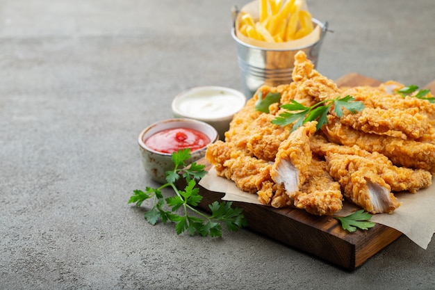Breaded chicken strips with two kinds of sauces and fried potatoes on a wooden board