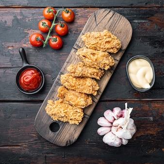 빵가루 입힌 닭 날개는 오래된 어두운 나무 탁자에 잘립니다.
