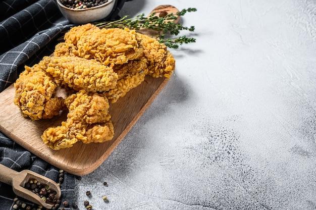 パン粉をまぶしたクリスピーフライドケンタッキーチキンウィング、おいしいディナー。灰色の背景