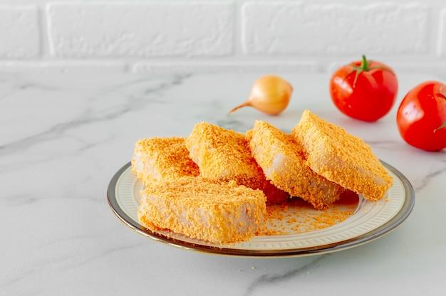 Панированные рыбные котлеты на тарелке, приготовленные для приготовления.