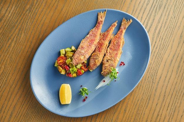 木製の壁にブループレートにアボカドとトマトのサラダのおかずとパン粉で揚げた海の魚(赤いボラ)。クローズアップ、セレクティブフォーカス