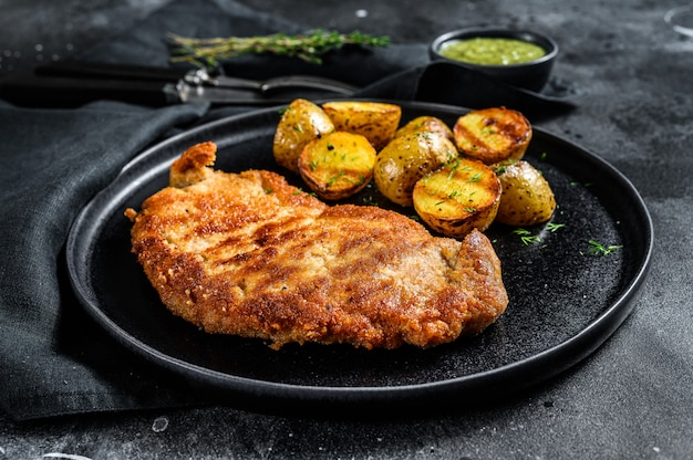 Breaded german weiner schnitzel with potatoes. black background. top view