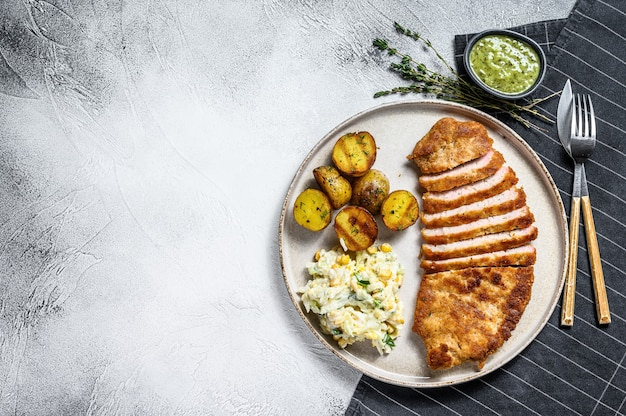 Breaded viennese schnitzel with baked potatoes and salad.  gray background