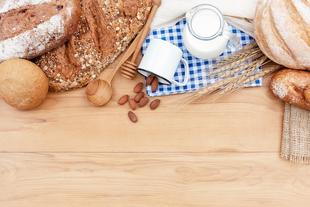 Breads and fresh milk with almond seed on wood table with free space. breakfast and bakery concept.