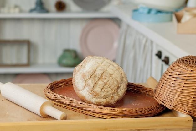Хлеб возле плетеной корзины на столе в деревенской кухне. композиция на кухне в фотостудии.
