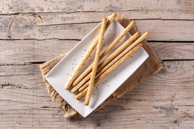 Закуска гриссини из хлебных палочек на деревенском деревянном столе