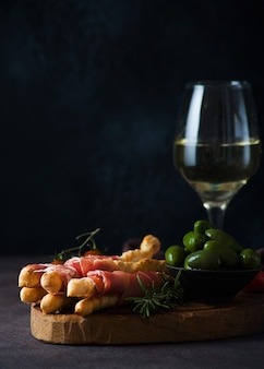 프로슈토, 올리브, 토마토를 곁들인 브레드스틱(그리시니) - 와인을 위한 전통적인 이탈리아 스낵, 선별적인 집중, 복사 공간