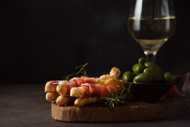 Breadsticks (grissini) with prosciutto, olives and tomatoes - traditional italian snacks for wine, selective focus, copy space