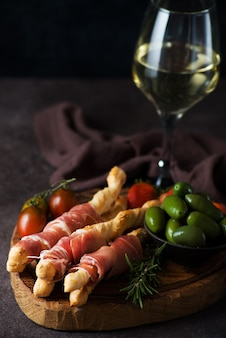 Breadsticks (grissini) with prosciutto, olives and tomatoes - traditional italian snacks for wine, selective focus