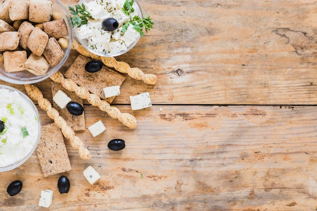 Breadsticks, olives, crisp bread and pastries with cheese bowl on wooden table