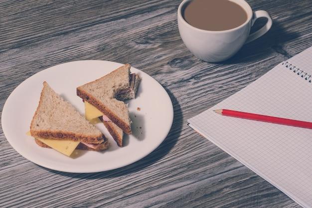직장에서 휴식. 하얀 접시에 물린 햄과 치즈 샌드위치, 뜨거운 흰색 커피 한 잔, 나무 탁자 위에 연필로 공책을 엽니다. 배경, 빈티지 효과