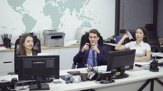 직장에서 휴식. 대기업 회사의 행복한 긍정적인 관리자는 휴식 시간에 즐거운 시간을 보냅니다. 스마트폰에서 놀고 종이 비행기를 던지고 컴퓨터에서 소셜 네트워크를 시청합니다.