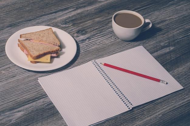 직장에서 휴식. 하얀 접시에 연필, 햄, 치즈 샌드위치, 나무 배경에 뜨거운 차 한 잔으로 카피북을 엽니다. 빈티지 효과