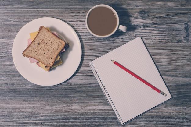 仕事で休憩。ホワイトコーヒー、ノートブック、鉛筆のカップとチーズサンドイッチの木製の背景。上面図