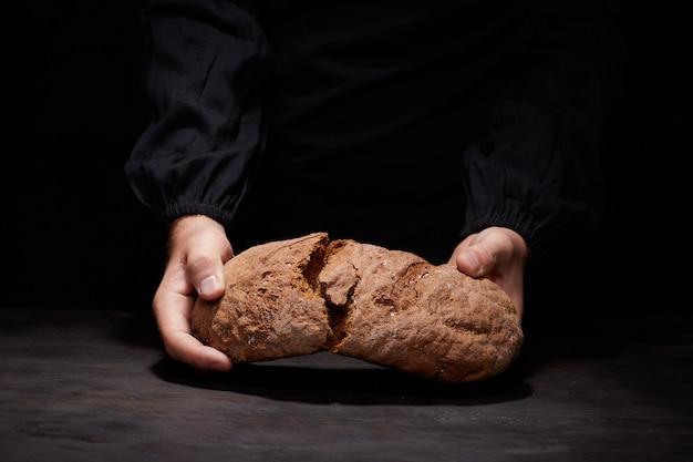 Break bread with me. cropped view of male chef breaking freshly baked sourdough bread