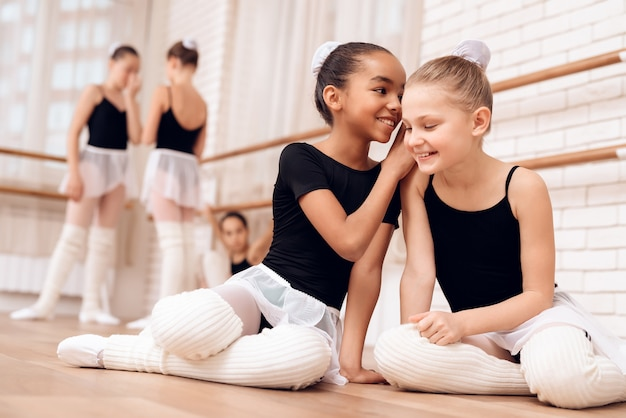 Break during ballet class happy kids talking.