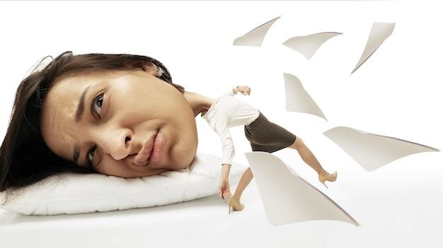 Rompi i sogni notturni come bicchieri. grande testa su piccolo corpo sdraiato sul cuscino. la donna in abito da ufficio non può svegliarsi ha mal di testa e ha dormito troppo. concetto di affari, lavoro, fretta, limiti di tempo.