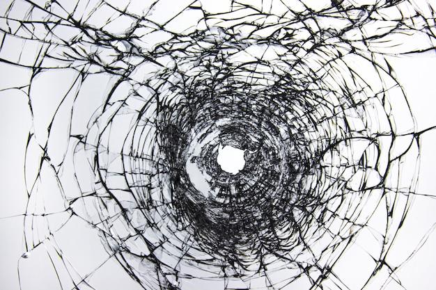 앞유리를 뚫습니다. 총기에서 구멍이 있는 깨진 유리. 강도와 파괴자에게 구타를 당한 후 창문에 금이 갔습니다. 샷 후 구멍이 있는 자동차의 투명한 앞유리.