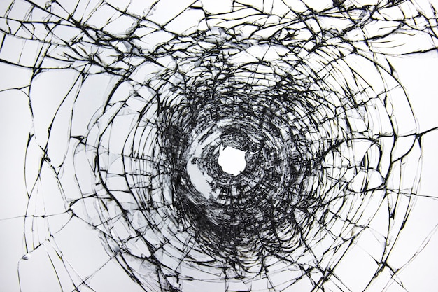 Break through the windshield. broken glass with a hole from a firearm. cracks on the window after being beaten by robbers and vandals. transparent windscreen of a car with a hole after the shots.
