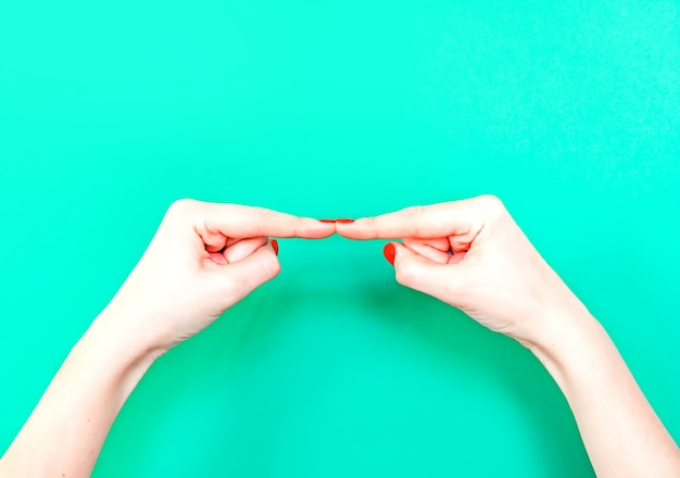 Break time hand gesture on isolated turquoise green color background