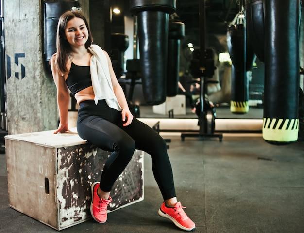 Перерыв. улыбающаяся девушка в спортивной одежде сидит на деревянной коробке в спортзале