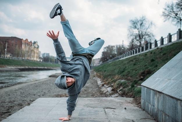 Breakdance performer, upside down motion on the street. modern dance style. male dancer
