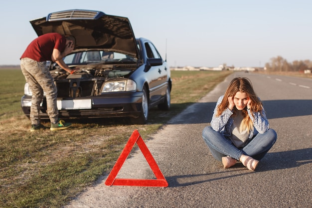 Breakdown alongside road. male tries to repair car, call by cell phone in road assistance, can`t solve problem by himself