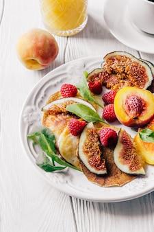 커피, 오렌지 주스, 무화과, 산딸기, 복숭아를 곁들인 접시로 아침 식사