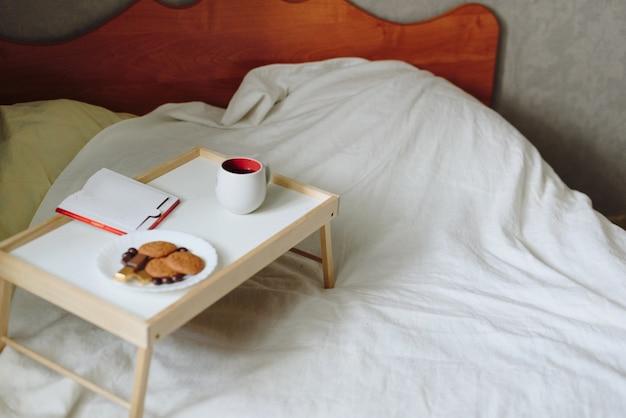 Завтрак и книга на кровати с белой простыней