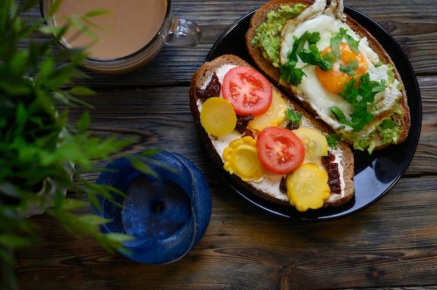 Завтрак и поздний завтрак два бутерброда с черным хлебом, с начинкой из сыра и овощей, лежат в черной тарелке, рядом с чашкой кофе с молоком, синей свечой и зеленым растением на деревянной