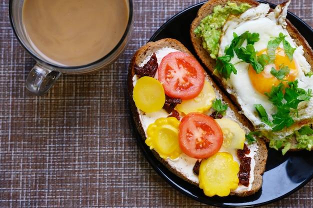 Завтрак и поздний завтрак два бутерброда с черным хлебом, с начинкой из сыра и овощей, лежат в черной тарелке, рядом с чашкой кофе с молоком на текстильном фоне