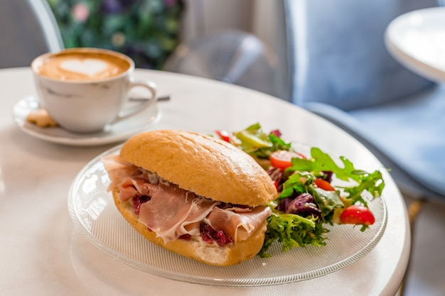 아침과 점심 - 샌드위치와 커피. 아름다운 라떼 아트가 있는 커피 한 잔, 텍스트를 위한 장소. 음식 개념입니다.