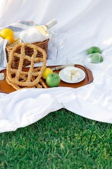 Завтрак на рассвете, на траве белый лист с подносом с сыром и виноградом, сухой хлеб, яблоко, лимон. романтическое настроение, эстетическая концепция медленного образа жизни, вид сверху