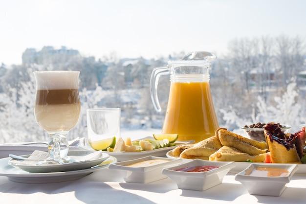 Завтрак в ресторане в снежную зиму на открытом воздухе.