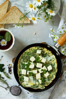 Breakfast background fried eggs with spinach feta cheese on stone table top view