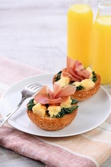 아침밥. 치즈, 시금치, 프로슈토, 오렌지 주스를 곁들인 구운 빵