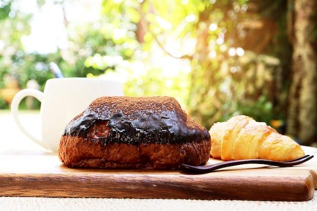 Завтрак хлебобулочные изделия с шоколадным кремом на вершине, круассаны на деревянной доске и белая чашка