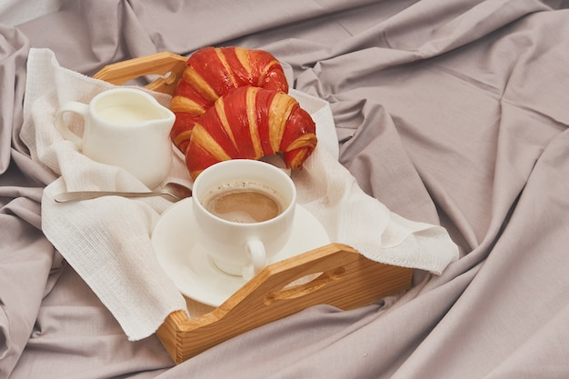 Breakfast in bed, coffee with cream, croissants in jam