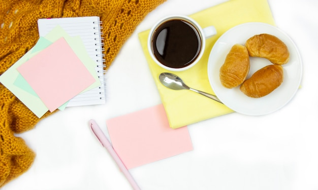 Breakfast in bed. flat composition with coffee, croissants and a notebook for writing. lifestyle frame. top view on sheets