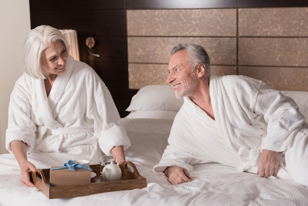 Breakfast in the bed. happy smiling aged couple lying on the bed and having a breakfast while expressing joy
