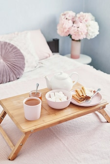 Breakfast in bed in hotel room. accommodation. breakfast in bed with tea cup with pancakes on tray