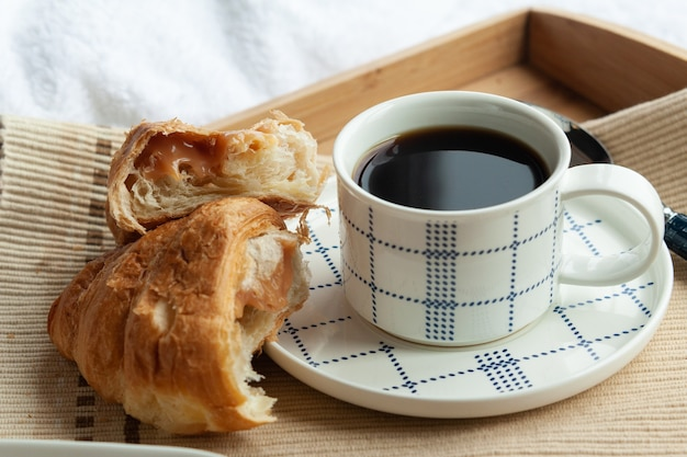 Breakfast in bed serving tray with croissant and cup of coffee in the hotel