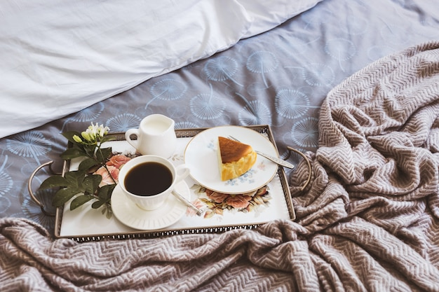 Breakfast in bed slice of cheesescake with cup of coffee and flower in a tray.
