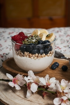 Breakfast in bed, table with a cup with blueberries, bananas, raspberries and yogurt top view