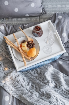Breakfast in bed, a tray with cheese, grissini, jam from young fir cones and a candle